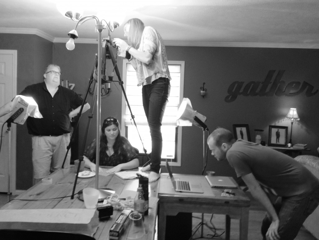 Tom (standing like normal people), Ashley (standing on a table) and Crouching Kyle film our origami artist. Please note: only one donut was harmed during filming.